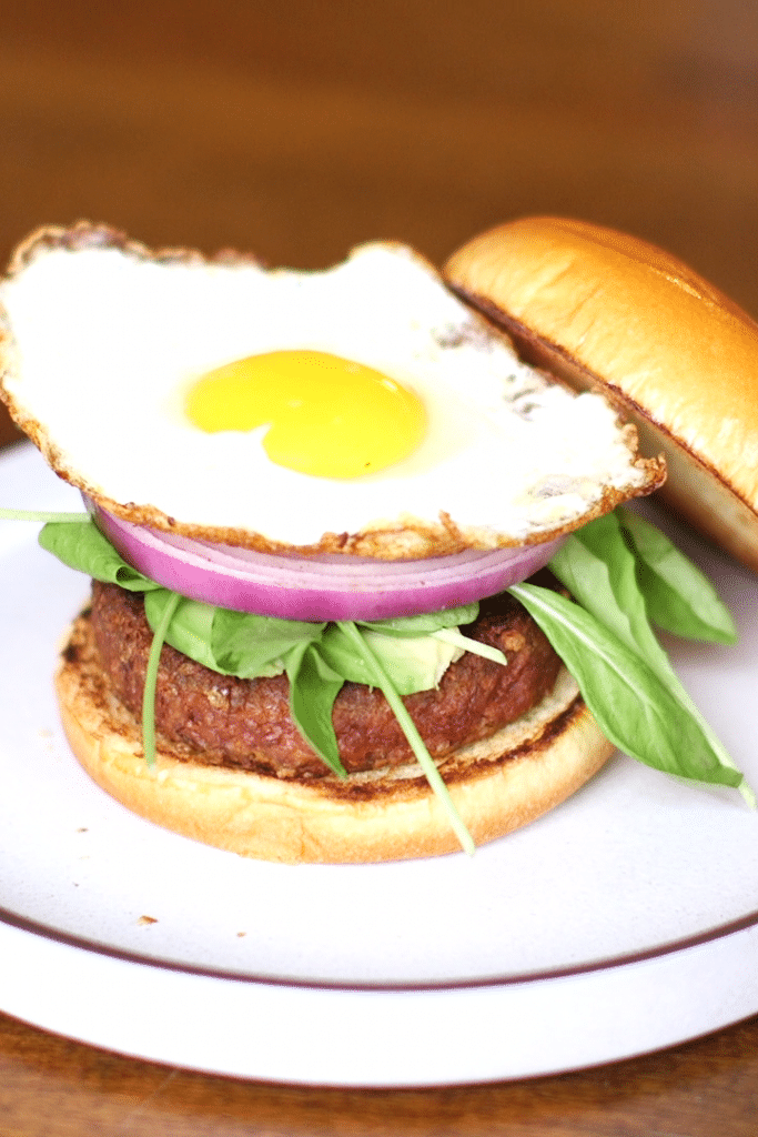 beyond burger with egg, lettuce, and onion on a bun